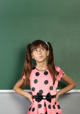 Pensive child girl near blank school blackboard stock images
