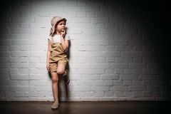 Pensive child in safari costume standing. At white wall royalty free stock photos