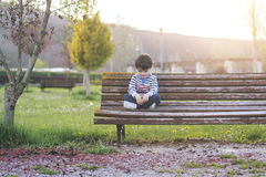 Pensive child. Thoughtful boy sitting in a park Stock Photo