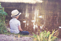 Pensive child. Thoughtful boy sitting by the river Royalty Free Stock Photos
