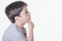 Pensive child. Thoughtful boy on white background Royalty Free Stock Photography