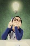 Pensive clever boy under light bulb Stock Photo