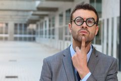 Pensive clever male with very thick eyeglasses.  Stock Photo