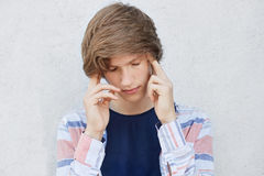 Pensive concentrated teenage boy with stylish haircut looking down thinking over something important. Fashionable male holding fin. Gers on temples trying to Royalty Free Stock Photos