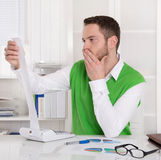 Pensive controller working with calculating machine at desk. Stock Images