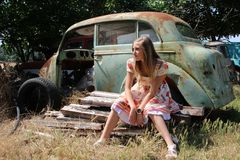 Pensive country girl from an old broken car Royalty Free Stock Image