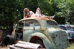 Pensive country girl from an old broken car Stock Photos
