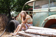 Pensive country girl from an old broken car Royalty Free Stock Photo