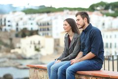 Pensive couple looking away on a ledge on vacation stock photography