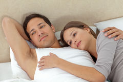 Pensive couple lying in each other's arms. On their bed Stock Images