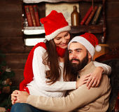 Pensive couple in New Year`s hats in Christmas at home Stock Photography
