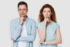 Pensive couple touch chin with finger thinking of something stock photos