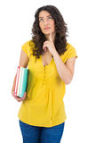 Pensive curly haired student holding notebooks Stock Image