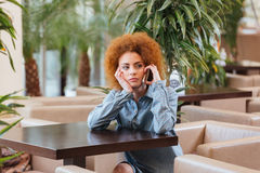 Pensive curly woman talking on cell phone in cafe Stock Photos
