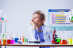 Pensive cute boy posing among chemical equipment Stock Image