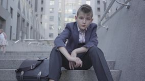 Pensive cute boy wearing business suit sitting on the stairs on the street. The boy is tired and wants to be just a stock video footage
