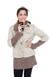 Pensive cute brunette in winter fashion holding smartphone Stock Images