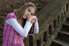 Pensive Cute Girl Leaning on Guitar and Looking at the Camera Royalty Free Stock Photography