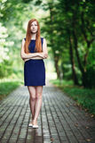 Pensive cute redhead girl in a blue dress on the park path Stock Images