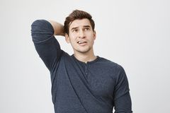 Pensive dark-haired man in long-sleeved t-shirt posing against gray background, frowns face, looks thoughtfully upwards. Scratches back of his head. Male model Stock Image