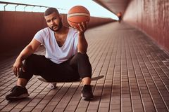 Portrait of a pensive dark-skinned guy dressed in a white shirt and sports shorts holds a basketball while sitting on a. Pensive dark-skinned guy dressed in a Royalty Free Stock Photo