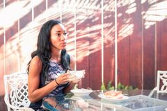 Pensive dark skinned woman having breakfast at the table on the. Outside terrace stock photo