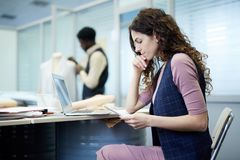Pensive designer thinking about fashion sketches. Serious pensive curly-haired designer in checkered waistcoat sitting at table with laptop and viewing paper stock photography