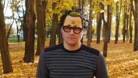 Pensive or dissatisfied man in a mask is in the autumn park. Leaf fall in a town in sunny day. Beautiful nature. Pensive or dissatisfied guy in a mask with curly stock footage