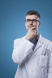 Pensive doctor with hand on chin Stock Image
