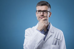 Pensive doctor with hand on chin Royalty Free Stock Images