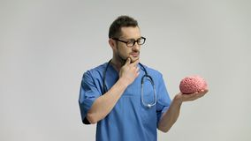 Pensive doctor holding a brain model and pointing up with his finger stock video