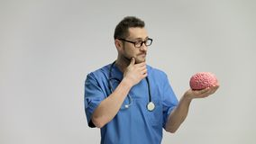Pensive doctor looking at a brain model stock footage