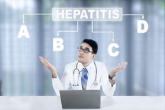 Pensive doctor looking at hepatitis word. Picture of a pensive male doctor working with laptop while looking at hepatitis word above his head Royalty Free Stock Photo