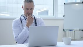 Pensive Doctor Thinking and Working on laptop stock images