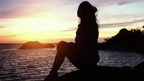 Pensive dreaming woman on beach looking at the sea during beautiful sunset. Slow Motion. 1920x1080. Pensive Dreaming Woman on Beach Looking at the Sea. Slow stock video footage