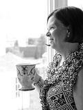 A pensive drink. Image of an older lady in thought while holding a drink Stock Photos