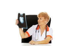 Pensive elderly female doctor looking for x-ray photo Stock Image