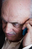 Pensive elderly man calling on the phone Stock Photo
