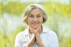 Pensive elderly woman. Walking in the summer park Stock Photo