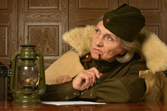 Pensive elderly woman. Writes a letter for home stock photo