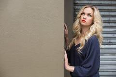 Pensive elegant blonde wearing classy dress posing outdoors Stock Photo