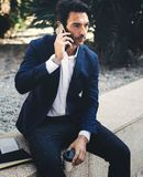 Pensive elegant businessman using contemporary smartphone while taking rest during work day.Holding hands take away. Coffee cup.Blurred background. Vertical Royalty Free Stock Photography