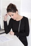 Pensive elegant secretary at desk at office. Royalty Free Stock Photos