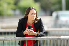 Pensive executive holding a phone outdoors Royalty Free Stock Images