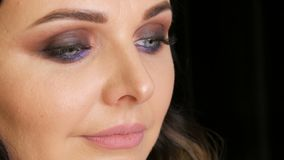 Pensive face of a beautiful young woman with professional makeup in the lilac tones, smoky eyes, close-up view stock video footage