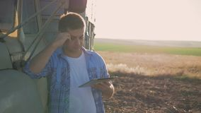 A pensive farmer is working in the field. Uses a tablet, stands near the agricultural engineering.