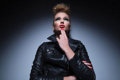 Pensive fashion woman in leather jacket is looking away Royalty Free Stock Photography