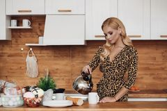 Pensive fashion young beautiful woman pouring water into mug holding teapot at kitchen interior
