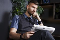Pensive fashionable confident young handsome man in chair with newspaper in luxurious interior. Rich man in private office in house reads news in newspaper royalty free stock photo