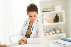 Pensive female doctor sitting at a desk in the office Stock Photos